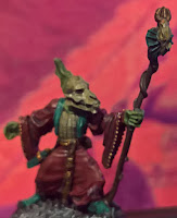 an image of V'shula, a T'skrang Nethermancer, staff in hand with a red temple n the background