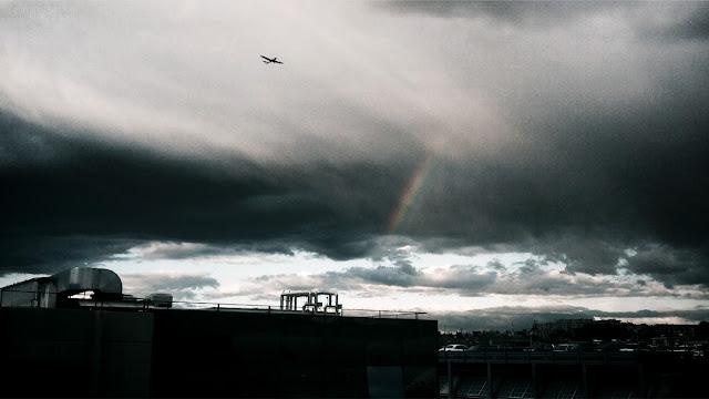 Fotografia di un aereo in volo in un cielo tempestoso con un arcobaleno