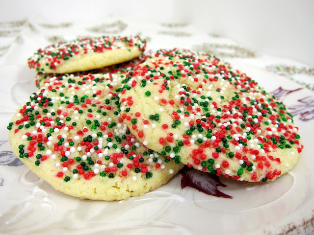 Soft Sugar Cookies - my favorite sugar cookie recipe. Great for the holidays! No rolling and cutting. Just shape into balls and bake. Butter, sugar, eggs, vanilla, almond extract, baking powders salt, flour and sprinkles. Can change the sprinkles according to the holidays and team colors. SO good! I could eat the whole batch! #cookies #cookierecipe #sugarcookies