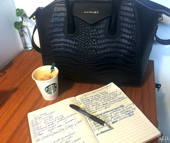 An image of a black givenchy handbag on a wooden table along with a money plant, starbucks coffee, note book and pen