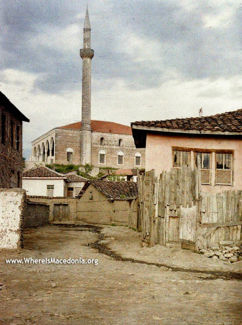 Middle-class houses and an alley of the former Skopje shopping district. The houses have wooden grilles on the windows, which is a characteristic of Turkish houses. They are built in uncooked brick.In the background, we see the mosque of Sultan Murad (still called Hunkar), preserved until today. The Sultan Murad Mosque was built in 1436 by Murad II, the father of Sultan Mehmed II the Conqueror, and is the work of Master Hussein of the city of Debar.It was rebuilt several times, at the time of Sultan Suleiman the Magnificent, that of Sultan Ahmed III, etc. The last reconstruction took place in 1912, with the financial support of the Sultan.It was built in the style of Bursa (Bush) but since then has undergone innumerable changes. On the north-west side, there is a four-column porch, whose aesthetically decorated capitals are linked by arches. The base of the building is square.On this site, we find nowadays individual houses of the residential part of the district of Bit-bazaar.
