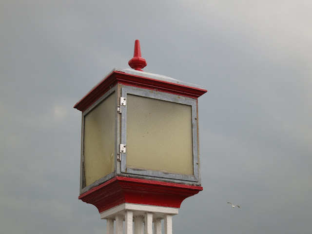 Large light that looks like lantern against grey sky with flying gull.