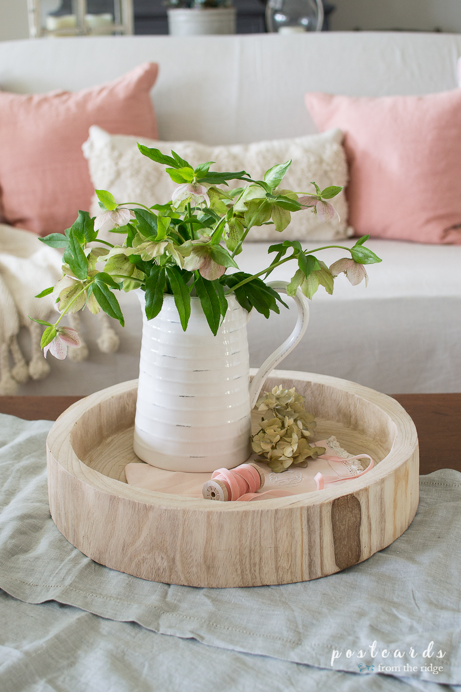Lenten roses in a white pitcher on a round wood tray