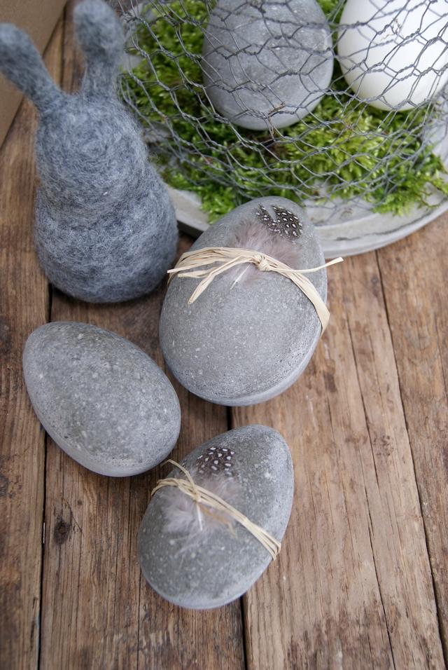 Ostereier aus Beton mit Federn und Bast dekoriert