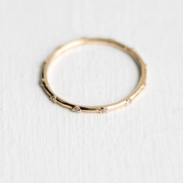 Handmade slim round band in 14k yellow gold with tiny diamonds set all the way around.