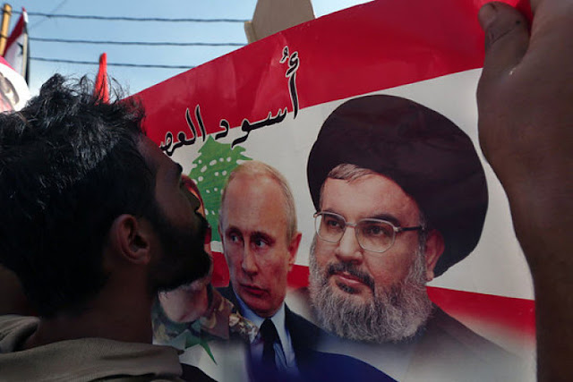 Image Attribute: A Syrian who lives in Lebanon kisses a poster with photos of Russian President Vladimir Putin and Hezbollah leader Sheikh Hassan Nasrallah during a rally in front of the Russian embassy in Beirut on October 18, 2015 / Bilal Hussein/AP