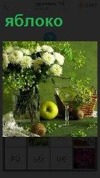 На столе стоит ваза с полевыми цветами, рюмка, корзинка и спелое яблоко
