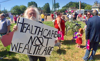 ADAPT activist holds a sign that says: Healthcare not Wealthcare
