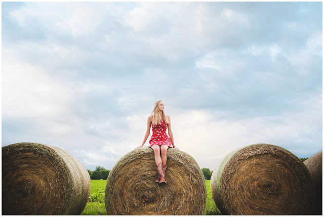 senior girl on bales of hay
