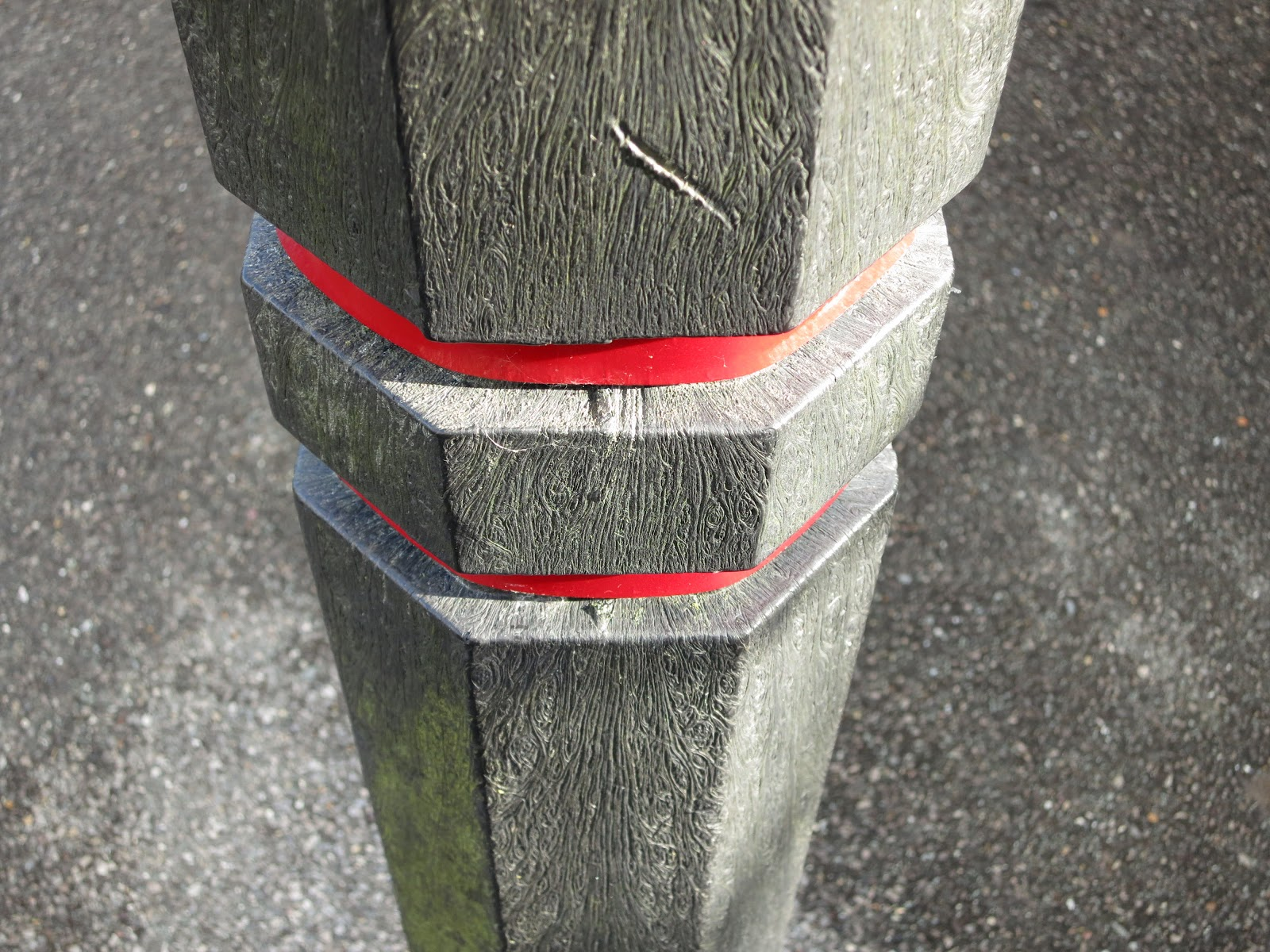 Scratched, plastic post with red bands