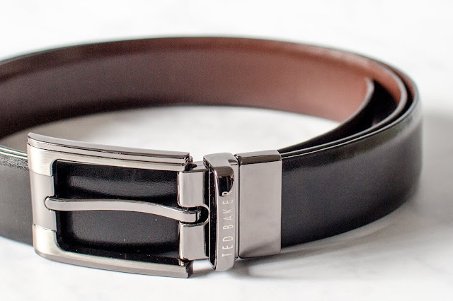 A close up image of a ted baker leather belt with silver buckle and reversible black and brown long belty bit