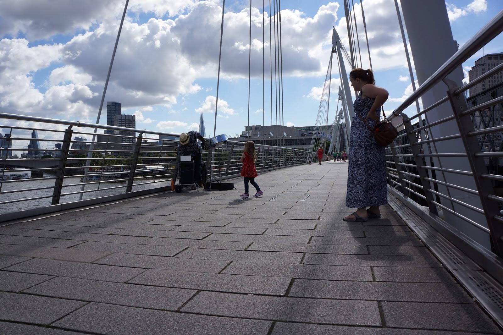 mum and daughter listening to a street performer on embankment bridge