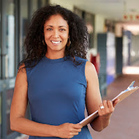 photo of a female teacher standing in a school hallway holding a clipboard and smiling directly at camera