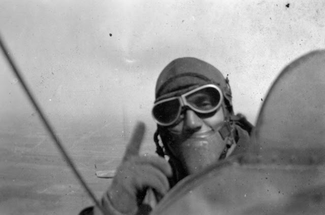 Snapshot of pilot instructor pointing up while flying, at Kelly Field in San Antonio TX, 1917. Photo taken with Kodak Vest Pocket Camera, designed to be small and convenient. Marketed to WWI soldiers. 'Make your own picture record of the war.' Dogfights and other stories of pilots. marchmatron.com