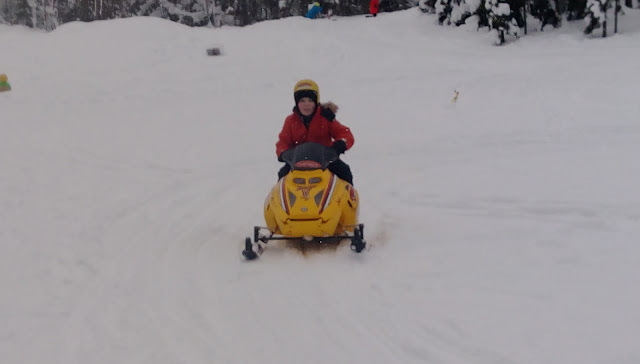 A child's snowmobile with male rider.