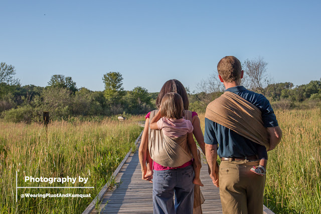 Image of a woman and a man on a board walk through marshy reeds. The woman has a child wrapped on her back in a gentle brown linen woven wrap carrier while the man has a toddler on his hip in a gentle brown linen ring sling carrier. Blue skies are up above and the lighting is of the setting summer sun.