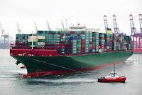 Bir römorkör büyük bir yük gemisini çekerken