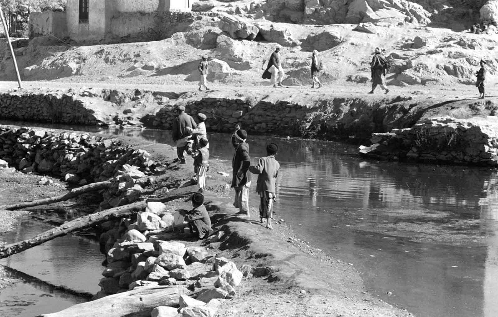 Los muchachos afganos juegan con cometas mientras los hombres pasan, en noviembre de 1959.