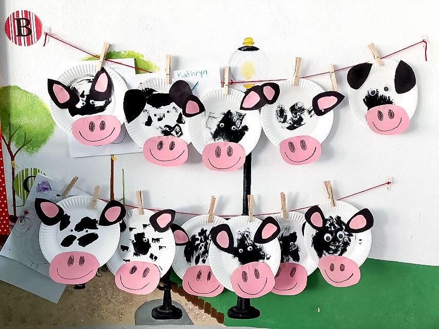 Preschool craft painted paper plate cow masks hanging up to dry