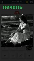 Девушка на берегу сидит с грустным видом и в печали