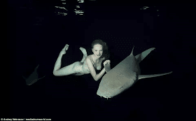 Young female model swims naked with sharks