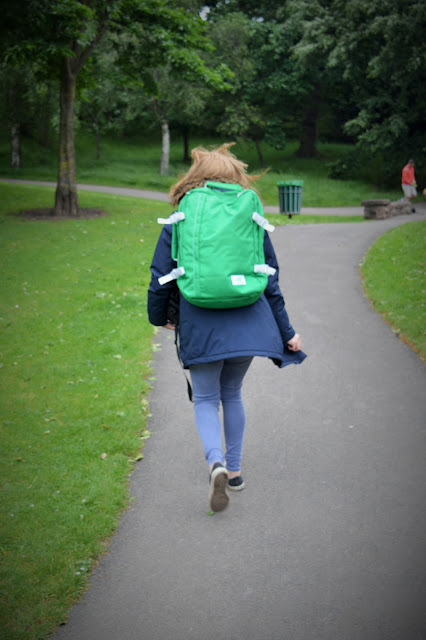 Woman walking away with green bag on her back.