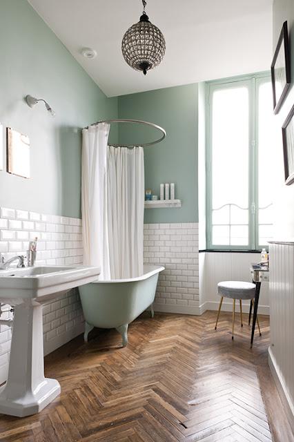 Salle de bain rétro avec parquet, carrelage métro, baignoire patte de lion et murs vert amande