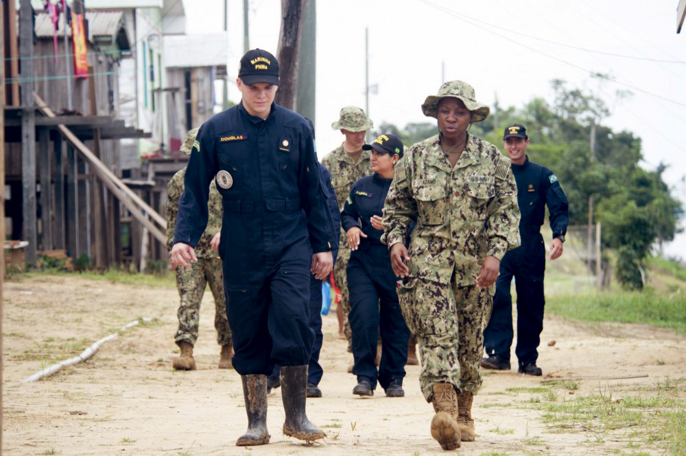 Members of the US and Brazil militaries walk and talk together in a village