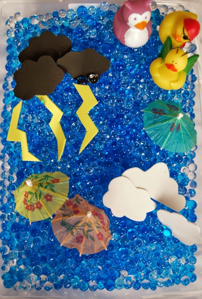 rainy day sensory bin with water beads, paper umbrellas, rubber ducks, foam clouds and lightning