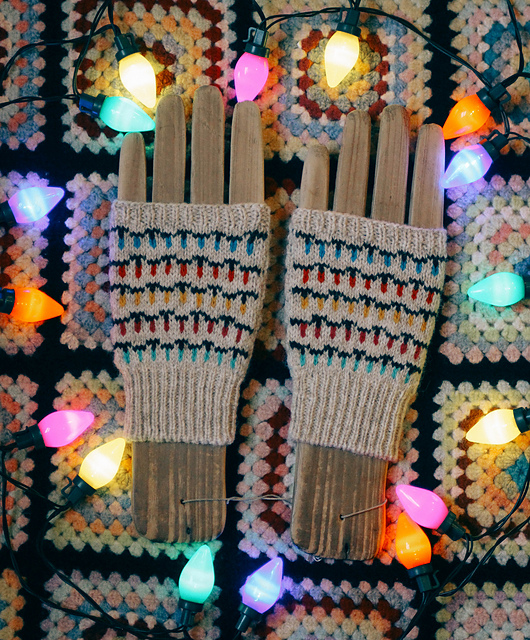 Fingerless gloves with old fashioned Christmas tree lights draped across them.