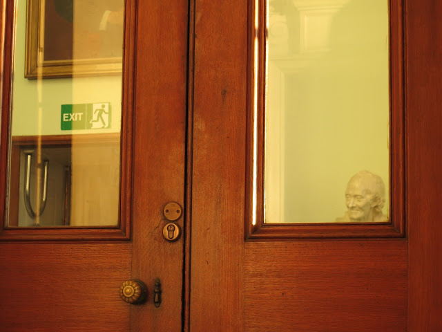 Bust of a smiling man beyond windows in polished wooden doors.