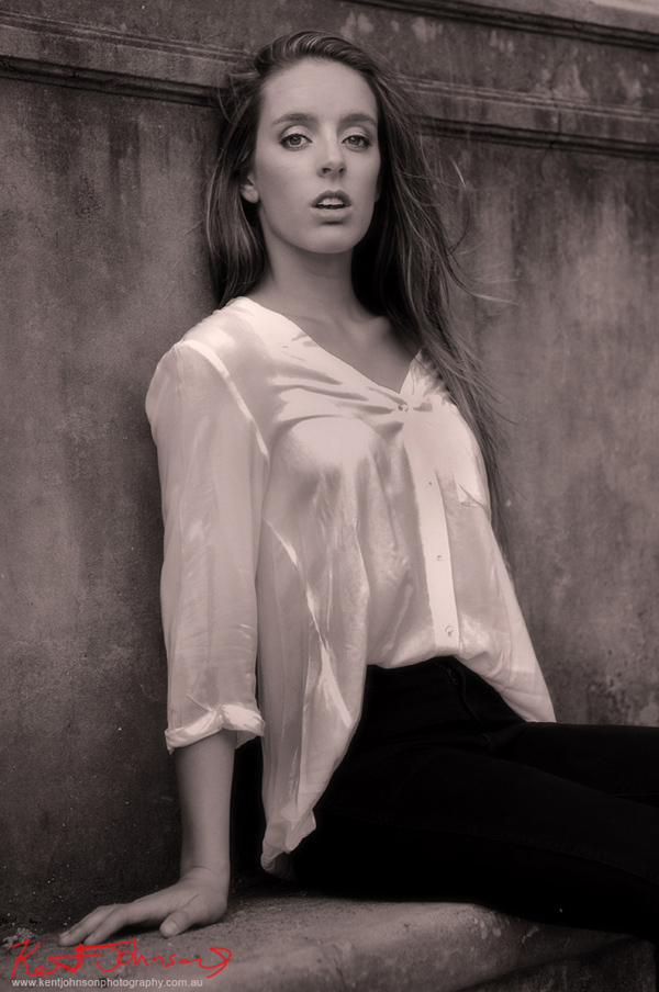 Black and white classic style seated portrait on location of a young woman in a white blouse. Modelling and Casting portfolio photography in Sydney by Kent Johnson.