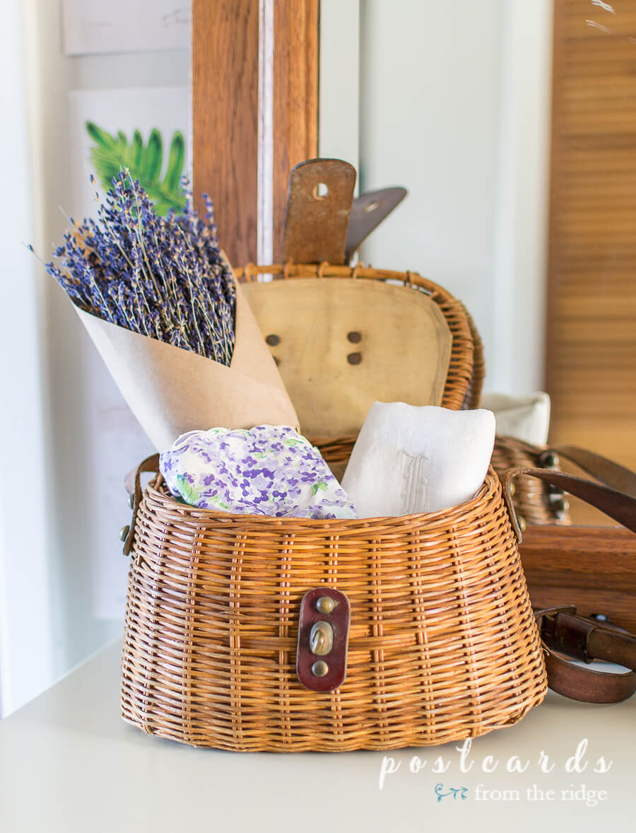 vintage linens and dries lavender in fishing creel basket
