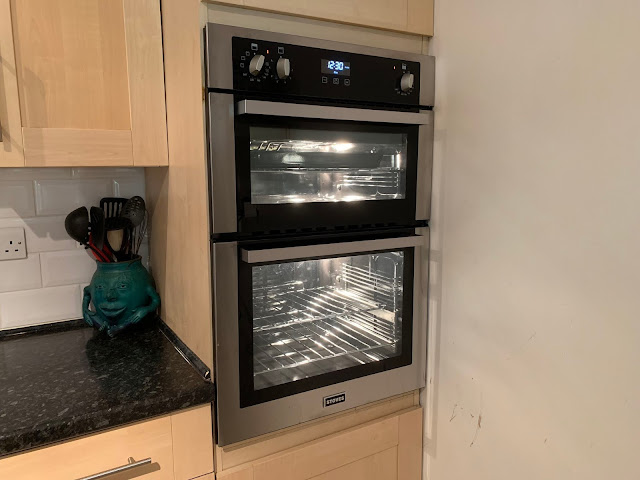 A new oven, turned on so all the lights are on and all shiny