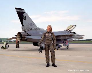 Foto em dia claro em parte de uma pista de pouso na base aérea do Alaska. Em foco, a Major Carey Jones, em pose para a foto, em pé, de frente em um largo sorriso, segura com a mão direita o capacete apoiado na coxa. Atrás, o imponente caça F-15 estacionado com inclinação à direita, canopy levantado, corpo médio prateado, asa curta com equipamento de bombardeio na extremidade, estabilizador vertical alto em preto e branco com pintura de um morcego com as asas abertas, abaixo, o prefixo: AF85 482, em seguida: SIOUX CITY e no topo lê-se:IOWA, a cauda é composta pelo motor de pós-combustão. A major Carey, é uma mulher jovem, loira, com cabelos presos, franja penteada à direita, rosto oval, sobrancelhas retas, olhos amendoados, nariz afilado, lábios médios e dentes alvos; ela usa um macacão militar verde amarronzado com zípers no peito e pernas, luvas, cinto de segurança do paraquedas nos ombros, extensões trespassadas na virilha e coturnos pretos. Ao fundo, à esquerda, dois apoiadores com equipamento para checagem de calibragem e além do gramado bem aparado,uma arborização desponta, finalizando em uma colina, à esquerda.