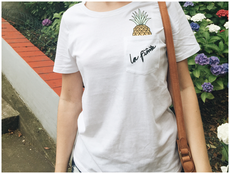 LA PINITA   June Gold wearing white pineapple printed H&M shirt and brown & Other Stories fringed bag