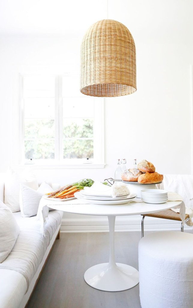 All white decor in a chic kitchen with Saarinen style tulip table, sofa, and natural wicker pendant light. Erin Fetherston's gorgeous all white California farmhouse with its white on white scheme is an inspiring lesson in Cali boho farmhouse chic with a Midcentury Modern twist. #allwhite #saarinen #whitekitchen #midcentury #breakfastnook