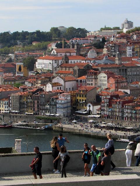 Pessoas circulando pela calçada do Jardim do Morro com vista para a cidade do Porto