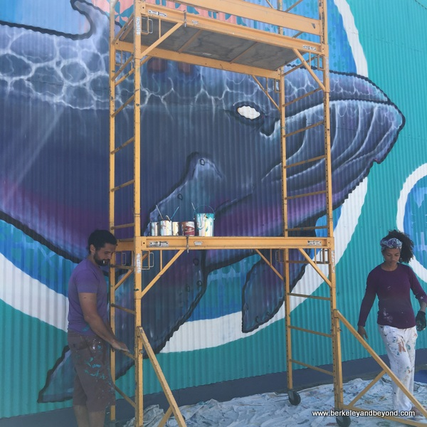 Alise and Jack Eastgate work on their whale mural at Jack London Square in Oakland, California