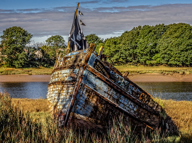 Photo of an old boat alongside the River Dee