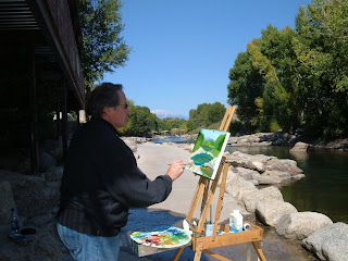 An artist paint outside along the river bank.