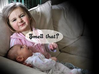 little girl holding stinky baby