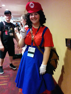A female cosplaying as a gender bent Mario from various Nintendo games. Shes wearing a red shirt, a blue skirt with suspenders, white gloves, and a red Mario hat complete with the white M logo.