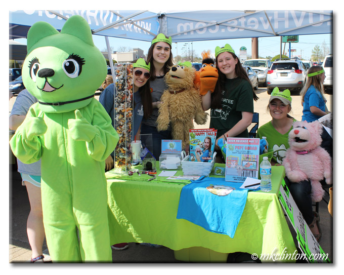 Person in green cat costume and other volunteers at pet adoption