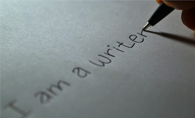 "the words ""I am a writer"" written on a piece of paper."