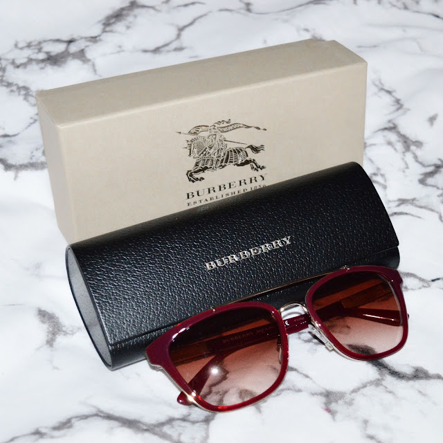 Burberry Sunglasses with black leather sunglasses case and beige Burberry box. Marble background