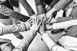 a photo of many hands in the middle showing cooperation