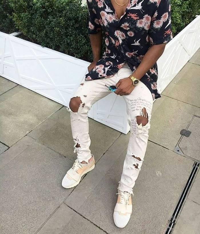 Look com camisa floral masculina e calça branca rasgada e escrita