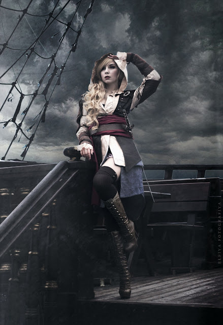 Female Steampunk pirate. This girl is wearing a hooded shirt, jacket, red sash, belt, knee socks and victorian lace up boots. women's steampunk pirate clothing.