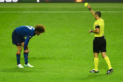 Marouane Fellaini is shown the yellow card for a bad foul